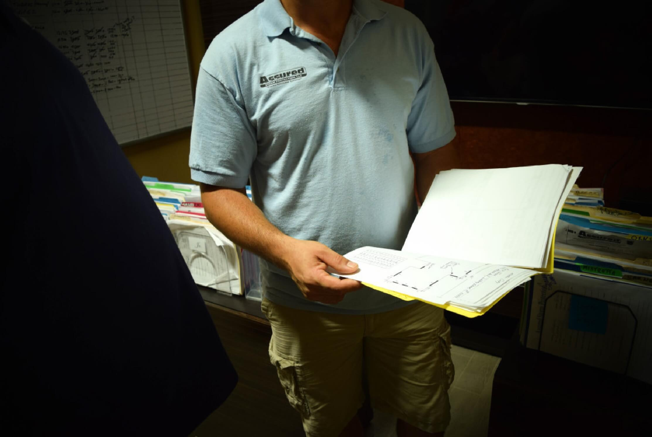 An assured storm protection engineer holding a file about a customer job